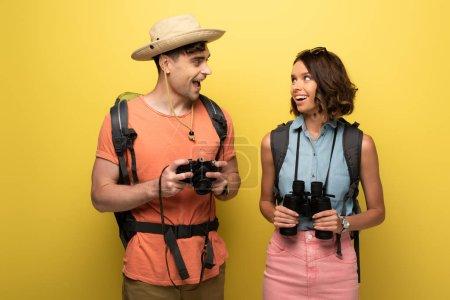 Photo pour Deux touristes gais avec des jumelles et l'appareil-photo numérique regardant l'un l'autre sur le fond jaune - image libre de droit