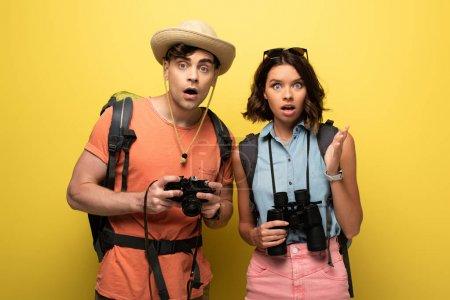 Photo pour Deux touristes choqués avec des jumelles et l'appareil-photo numérique regardant l'appareil-photo sur le fond jaune - image libre de droit