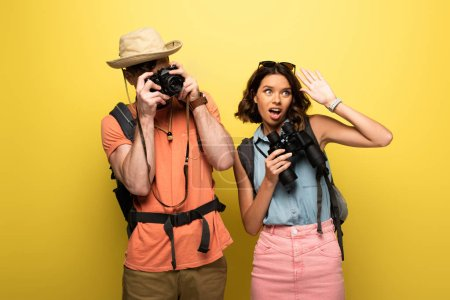Photo for Man taking photo with digital camera while standing near young woman waving hand and looking away on yellow background - Royalty Free Image
