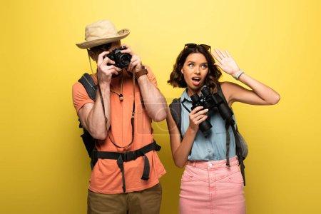Photo pour Homme prenant la photo avec l'appareil-photo numérique tout en restant près de la jeune femme agitant la main et regardant loin sur le fond jaune - image libre de droit