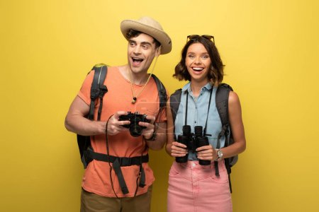 Photo for Two smiling tourists holding digital camera and binoculars on yellow background - Royalty Free Image