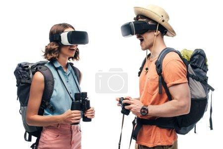 Photo pour Deux touristes gais regardant les uns les autres tout en utilisant des casques de réalité virtuelle isolés sur le blanc - image libre de droit