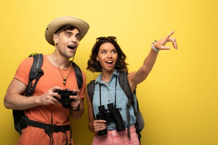 Photo pour Cheerful young woman pointing looking away and pointing with finger while standing near surprised man on yellow background - image libre de droit