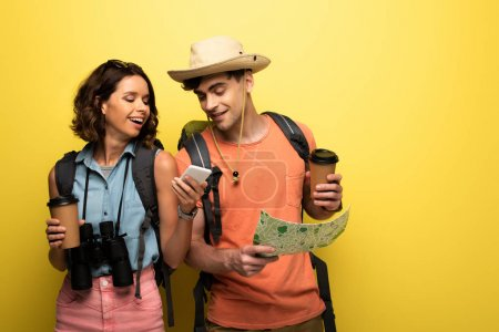 Photo for Cheerful woman showing smartphone to man with geographic map on yellow background - Royalty Free Image