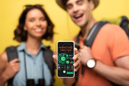Photo pour Foyer sélectif de la femme gaie affichant le smartphone avec l'application d'analyse de marketing tout en restant près de l'homme de sourire sur le fond jaune - image libre de droit