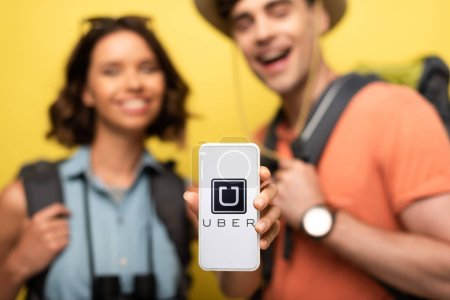 Photo pour KYIV, UKRAINE - JUNE 3, 2019: Selective focus of cheerful woman holding smartphone with UBER app while standing near smiling man on yellow background. - image libre de droit