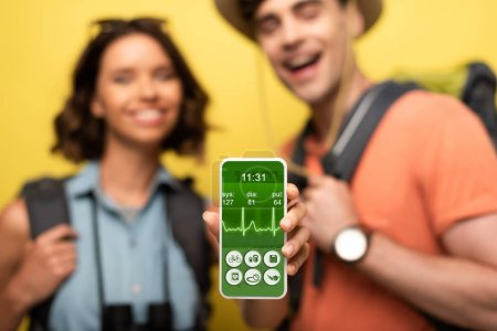 Photo for Selective focus of cheerful woman showing smartphone with heartbeat rate app while standing near smiling man on yellow background - Royalty Free Image