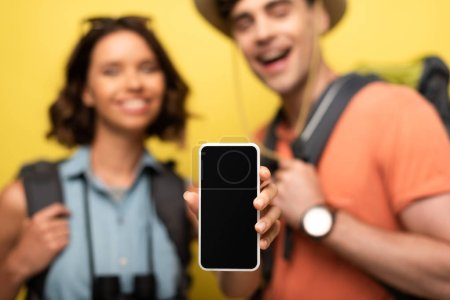 Foto de Selective focus of cheerful woman showing smartphone with blank screen while standing near smiling man on yellow background - Imagen libre de derechos