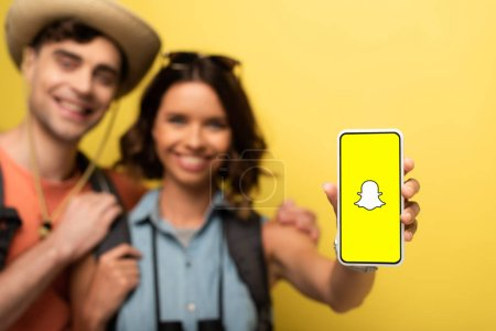 Photo for KYIV, UKRAINE - JUNE 3, 2019: Selective focus of smiling girl standing near cheerful boyfriend and showing smartphone with Snapchat app on yellow background. - Royalty Free Image