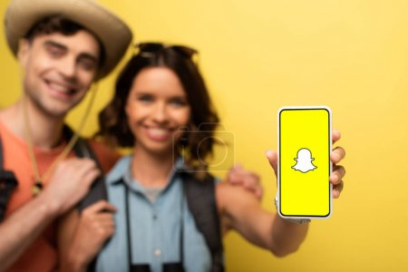 KYIV, UKRAINE - 3 JUIN 2019 : Mise au point sélective d'une fille souriante debout près de son petit ami joyeux et montrant son smartphone avec l'application Snapchat sur fond jaune .