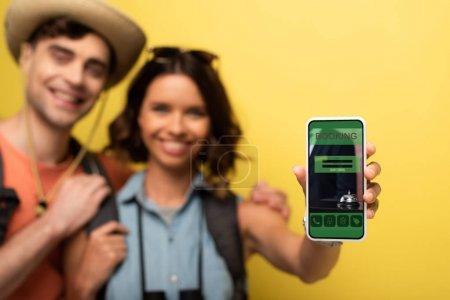 Photo pour Foyer sélectif de la fille de sourire restant près du petit ami gai et montrant le smartphone avec l'application de réservation sur le fond jaune - image libre de droit