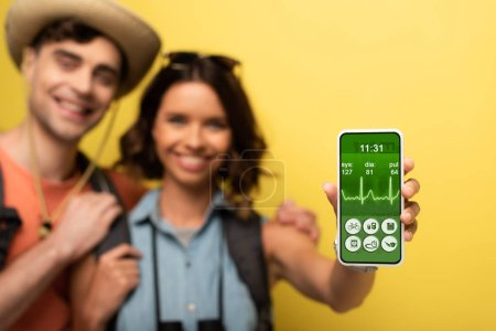 Foto de Selective focus of cheerful young woman standing near smiling boyfriend and showing smartphone with heartbeat rate app on yellow background - Imagen libre de derechos