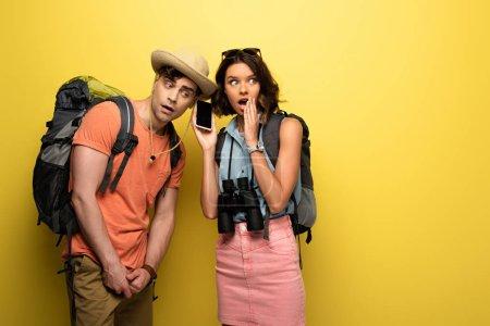 Photo pour Choqué jeune femme tenant smartphone avec écran vide près homme réfléchi sur fond jaune - image libre de droit