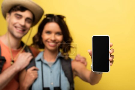 Photo pour Selective focus of cheerful young woman standing near smiling boyfriend and showing smartphone with blank screen on yellow background - image libre de droit