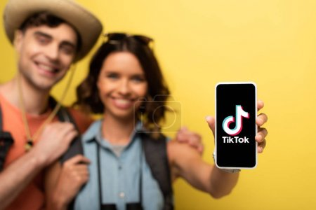 Photo pour KYIV, UKRAINE - JUNE 3, 2019: Selective focus of cheerful young woman standing near smiling boyfriend and showing smartphone with Tik Tok app on yellow background. - image libre de droit
