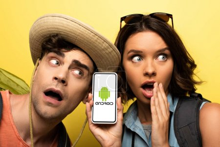 Photo for KYIV, UKRAINE - JUNE 3, 2019: Surprised young woman showing smartphone with Android app while standing near shocked man on yellow background. - Royalty Free Image