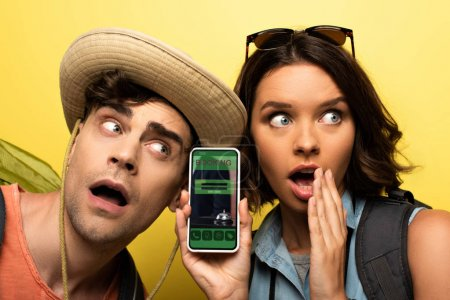 Foto de Surprised young woman showing smartphone with booking app while standing near shocked man on yellow background - Imagen libre de derechos