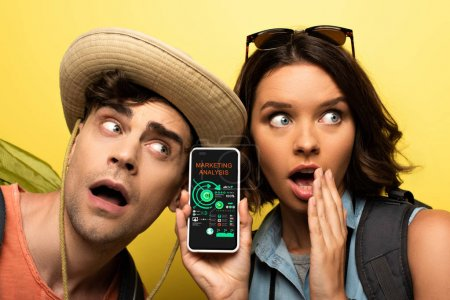 Photo pour Jeune femme choquée affichant le smartphone avec l'application d'analyse de marketing tout en restant près de l'homme étonné sur le fond jaune - image libre de droit