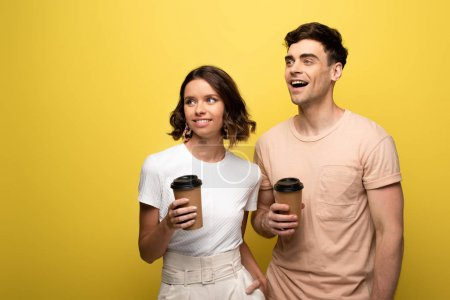 Photo for Cheerful man and woman holding disposable cups while looking away on yellow background - Royalty Free Image