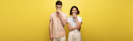 Photo for Panoramic shot of young man and woman drinking coffee to go while looking at camera on yellow background - Royalty Free Image