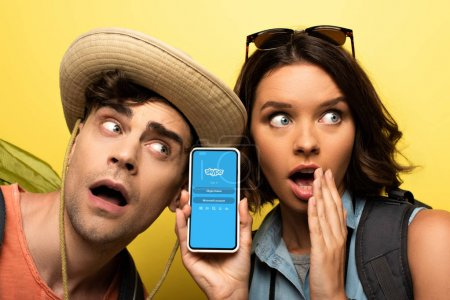 Photo for KYIV, UKRAINE - JUNE 3, 2019: Shocked young woman showing smartphone with Skype app while standing near surprised man on yellow background. - Royalty Free Image