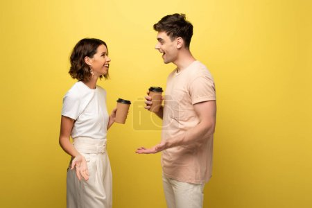 Photo for Smiling man and woman talking while holding paper cups on yellow background - Royalty Free Image