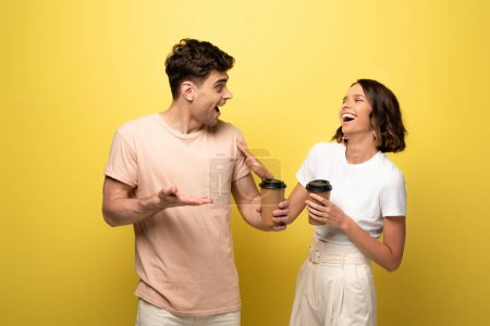 Photo pour Homme et femme excités parlant tout en retenant le café pour aller sur le fond jaune - image libre de droit