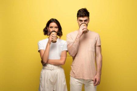 Photo pour Jeune homme et femme buvant du café pour aller tout en buvant le café pour aller sur le fond jaune - image libre de droit