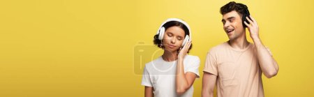Photo for Panoramic shot of young man and woman listening music in headphones on yellow background - Royalty Free Image