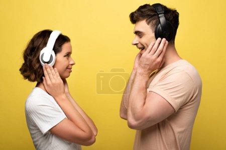 Photo pour Homme et femme joyeux écoutant de la musique dans les écouteurs tout en se regardant sur fond jaune - image libre de droit