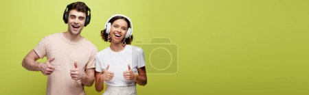 Photo for Panoramic shot of excited man and woman smiling at camera and showing thumbs up on green background - Royalty Free Image