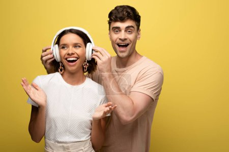 Photo for Smiling man putting on headphones on cheerful girl on yellow background - Royalty Free Image