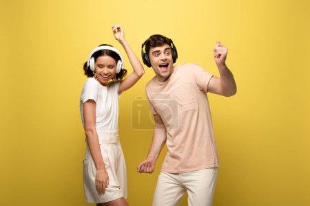 Foto de Excited man and woman dancing while listening music in headphones on yellow background - Imagen libre de derechos