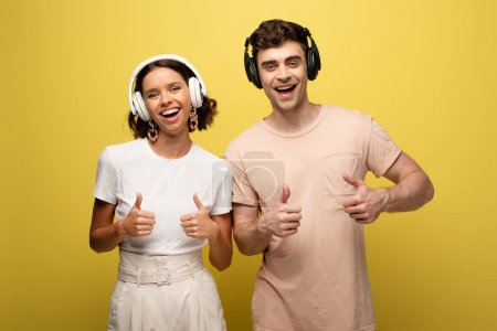 Foto de Cheerful man and woman showing thumbs up while smiling at camera on yellow background - Imagen libre de derechos