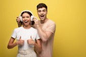 """Постер, картина, фотообои """"cheerful man putting on headphones on excited girl while looking at camera together on yellow background"""""""