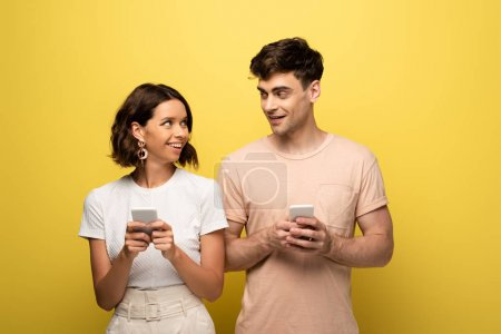 Photo for Positive man and woman looking at each other while using smartphones on yellow background - Royalty Free Image