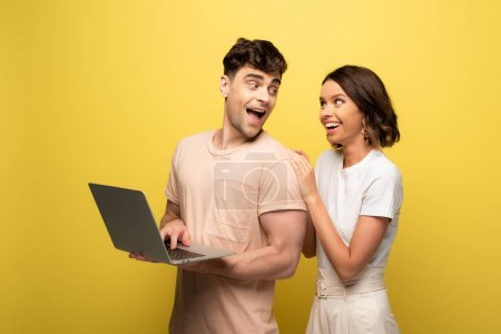 Photo pour Happy young man using laptop while standing near cheerful girl on yellow background - image libre de droit