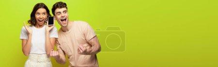 Photo pour Plan panoramique de jeune homme heureux montrant geste oui tout en se tenant près de fille excitée sur fond vert - image libre de droit
