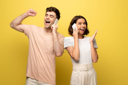 Photo for Cheerful man and woman talking on smartphones and looking away on yellow background - Royalty Free Image