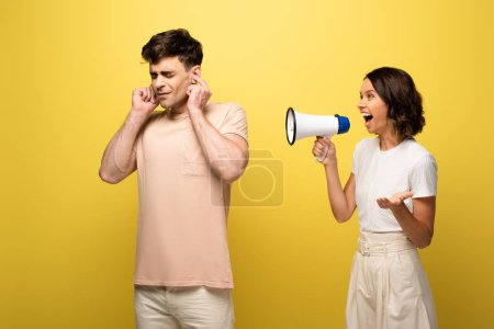 Photo for Irritated girl quarreling in loudspeaker at boyfriend on yellow background - Royalty Free Image