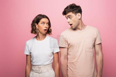 Photo pour Jeunes couples se disputant tout en regardant l'un l'autre sur le fond rose - image libre de droit