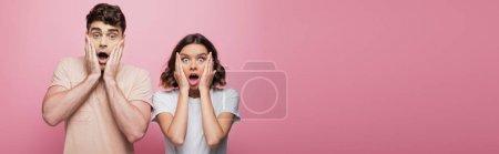 Photo pour Prise de vue panoramique de l'homme et de la femme choqués tenant la main près du visage tout en regardant la caméra sur fond rose - image libre de droit