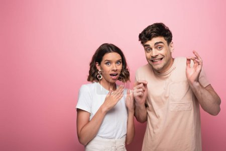 Photo for Emotional man and woman gesturing shut up while looking at camera on pink background - Royalty Free Image