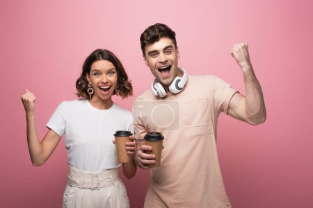 Photo for Excited man and woman showing yes gestures while holding paper cups and looking at camera on pink background - Royalty Free Image