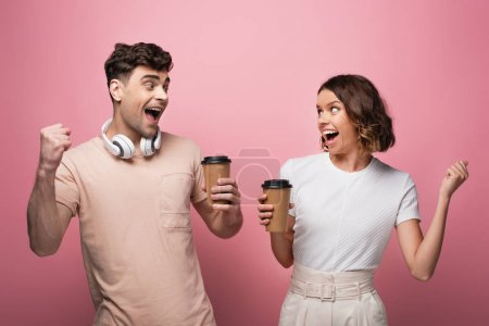 Foto de Happy man and woman showing yes gestures while holding paper cups and looking at each other on pink background - Imagen libre de derechos