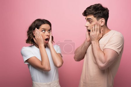 shocked man and woman holding hands near faces while looking at each other on pink background