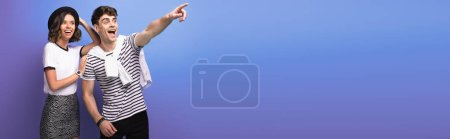 Foto de Panoramic shot of excited man looking away and pointing with finger near smiling girlfriend on blue background - Imagen libre de derechos