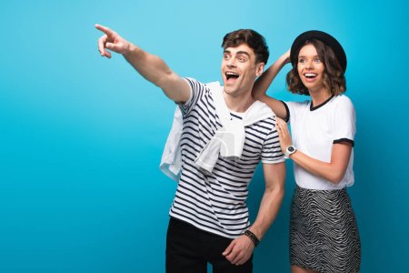 Foto de Excited man looking away and pointing with finger near smiling girlfriend on blue background - Imagen libre de derechos
