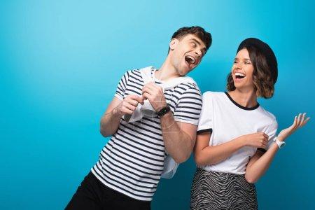 Photo pour Homme et femme à la mode et excitériant ensemble sur le fond bleu - image libre de droit