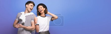 Photo for Panoramic shot of young, cheerful couple laughing together on blue background - Royalty Free Image